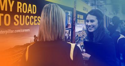 2 women talking, in front of a poster reading my road to success